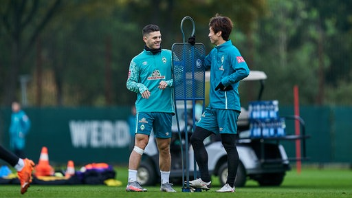 Milot Rashica und Yuya Osako plaudern locker am Rande des Trainings.